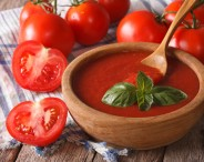 red tomato ketchup and basil in a wooden bowl closeup. horizontal